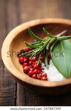 Close up on the fresh rosemary sprig in a rustic olive wood bowl with red peppercorns, bay leaf and kosher salt. Shallow DOF - stock photo