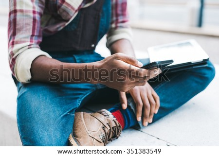 Close up on the hand of a young handsome afro black man using a smartphone, tapping the screen - technology, social network, communication concept - stock photo