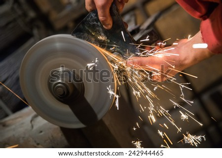 Close up on the hands of a blacksmith sharpening an ax on an electrical grinder - stock photo