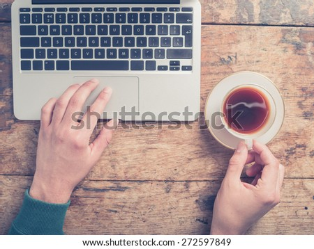 Close up on the hands of a man as he is using a laptop and having a cup of coffee at a wooden table - stock photo