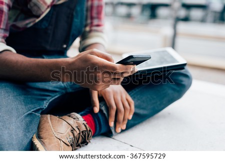 Close up on the hands of a young handsome afro black man using a smartphone, tapping the screen - technology, social network, communication concept