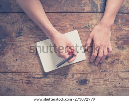 Close up on the hands of a young woman as she is writing in a small notepad at a wooden table - stock photo