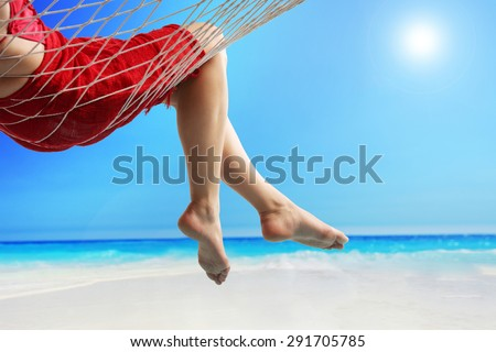 Close-up on the legs of a woman lying in a hammock on a beach by the open sea - stock photo