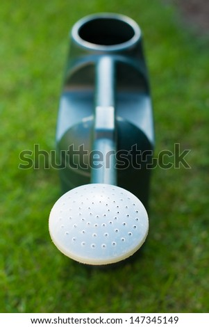 Close up on the spout of a green plastic watering can against some bright green grass - stock photo