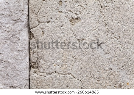 Close up on the texture of cracks and crevices in an ancient, sun-withered stone wall. Two-dimensional surface structure for use as solid background. Outdoor shot with camera mounted on tripod. - stock photo