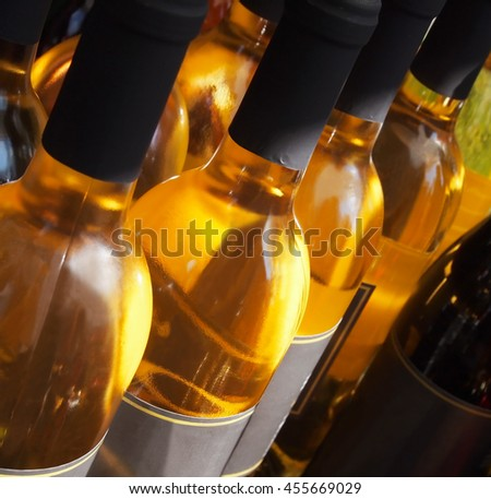 Close up on the top and necks of a row of white wine bottles on a table outside.