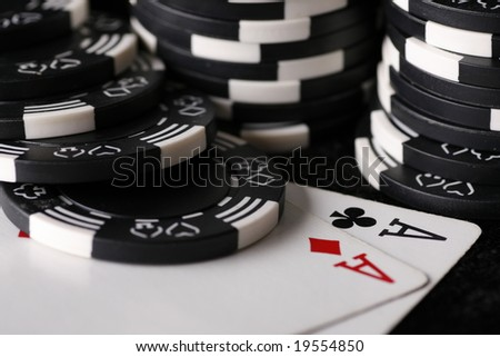 Close up on the very best starting hand in texas holdem poker with casino chips in background. - stock photo
