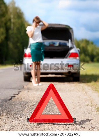 Close up on triangle warning sign with woman calling for assistance after breaking down with her car on background