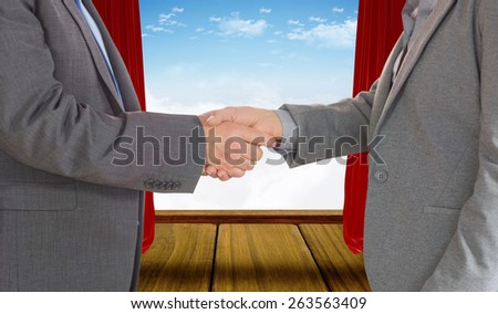 Close up on two businesspeople shaking hands against stage with red curtains - stock photo