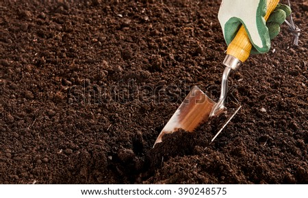 Close up on unidentified hand in rubber and cloth glove using steel trowel to dig into bare soil garden - stock photo