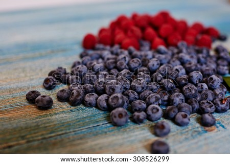 Close-up on vintage table sprinkled a handful of fresh raspberries and blueberries - stock photo