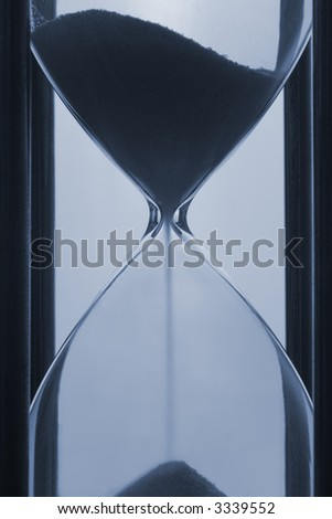 Close up on waist of sand glass with sand running. Backlit, on light coloured background, blue toned. - stock photo