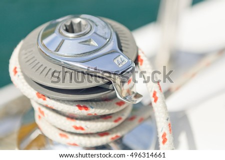 Close up on winch and rope of yacht over blue sea