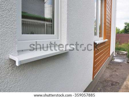 Close up on Window in New Modern Passive House Plaster and Wooden Facade Wall with Rain Gutter - stock photo