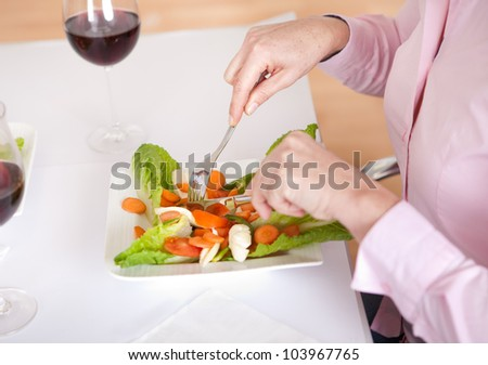 Close-up on woman eating salad at home