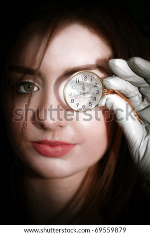Close Up On Woman Face Holding Monocle To Eye - stock photo