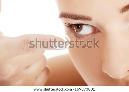Close up on woman putting lens into eye. Over white background. - stock photo