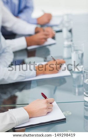 Close up on workmates taking notes during presentation in bright office