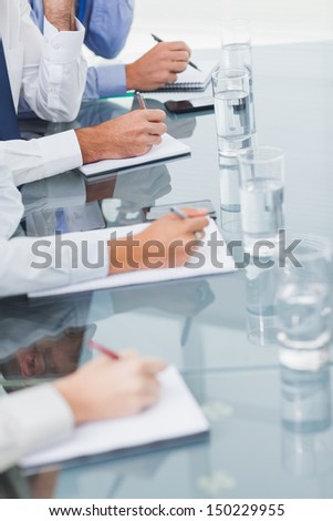 Close up on workmates taking notes while attending presentation in bright office - stock photo