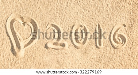 Close up on 2016 written in the sand of a beach with a heart - stock photo