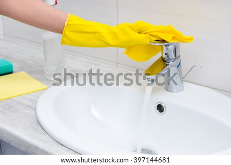 Close up on yellow rubber gloved hand checking water flow from chrome faucet into ivory colored sink with spray bottle and sponges beside it - stock photo