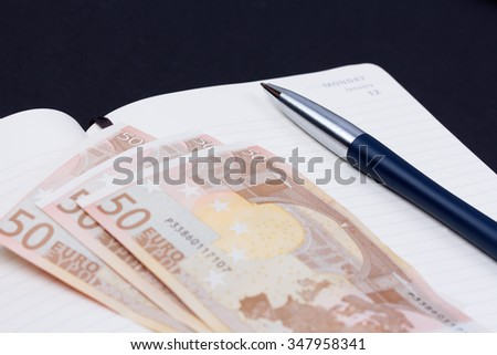 Close up open daily planner with luxury ball pen and some euro banknotes on black background. - stock photo