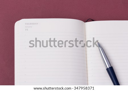 Close up open daily planner with luxury ball pen on red background. - stock photo