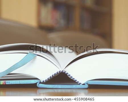 Close up open text book on wood table in the library with blurred bookshelf background, Blue cover vintage tone
