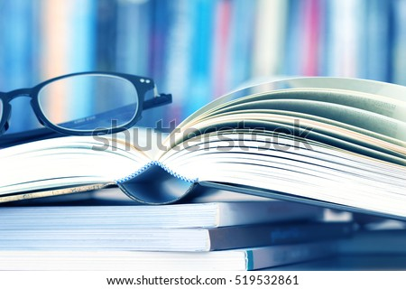 Close up opened book page and reading eyeglasses with blurry bookshelf background for education and publication concept