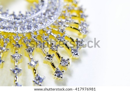 close up or macro of diamonds in a golden jewelry with white background. - stock photo