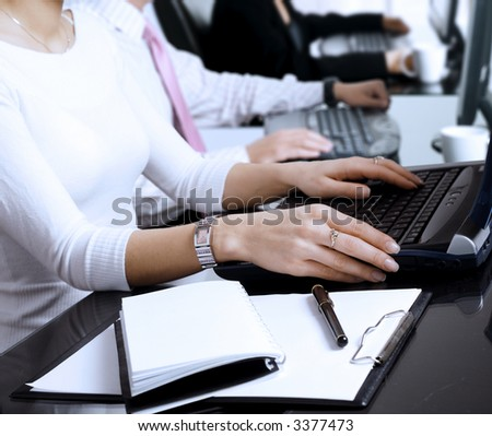 Close-up os human hands. Young office workers are typing on keyboards in front of their office computers. - stock photo