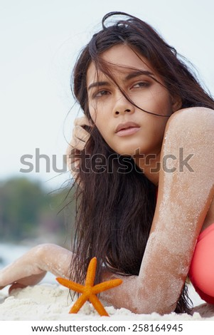 Close up outdoor facial portrait young asian model on the white sand with shell - stock photo