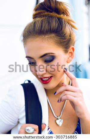 Close up outdoor fashion portrait of pretty young elegant woman walking alone at the street after business work, wearing stylish outfit and jewelry, bright sexy smoke makeup. - stock photo