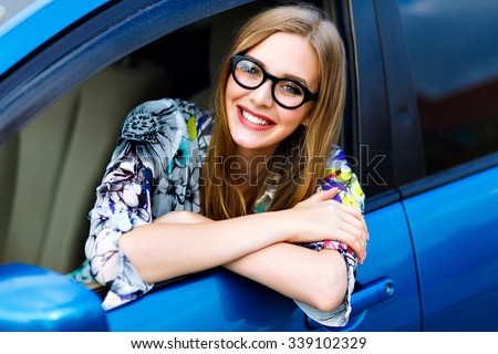 Close up outdoor lifestyle travel photo of young blonde hipster  woman driving car, glasses and bright clothes, big smile happy mood, enjoy her nice day, young businesswoman . - stock photo