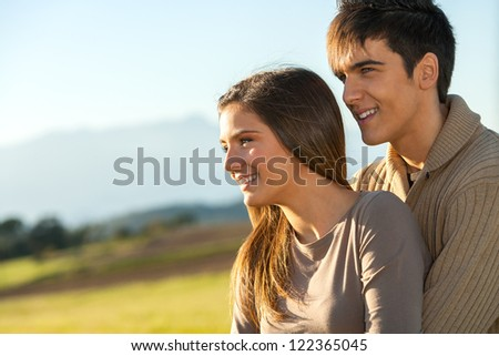 Close up outdoor portrait of boy showing girlfriend something in the distance. - stock photo