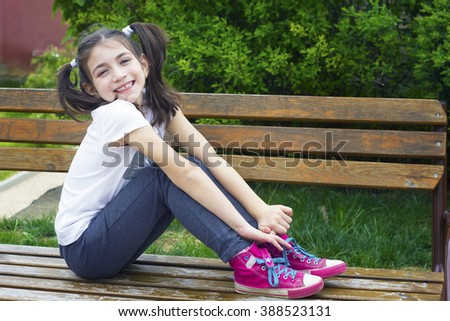 Close-up outdoor portrait of smiling little girl sitting on a bench in park - stock photo