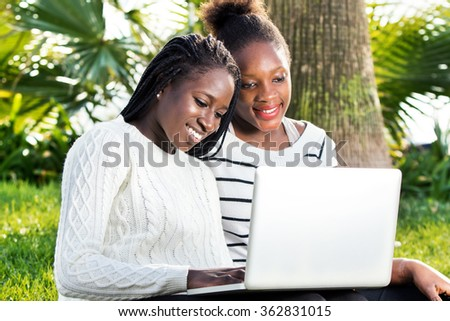 Close up outdoor portrait of two African teen girls typing on laptop in park.