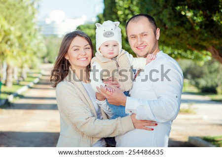 Close up outdoors portrait of happy family wearing casual. Mom and dad holding little kid with funny hat. - stock photo