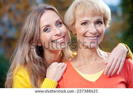 Close up outdoors Portrait of pretty Senior Woman With her adult smiling Daughter In Park - stock photo