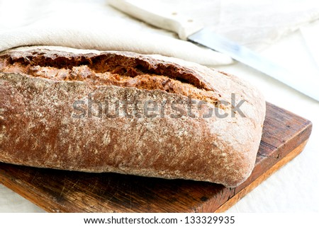 Close-up oven baked home made bread on cutting board - stock photo