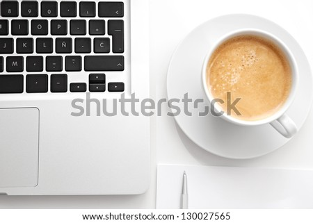 Close up over head view of a white work desk interior with a laptop computer, a cup of coffee, blank paper and a pen.