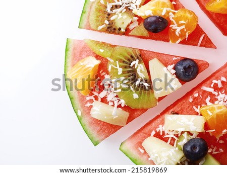 Close up overhead detail of a slice of tropical fruit watermelon pizza topped with kiwifruit, blueberries, orange, pineapple, and sprinkled with desiccated coconut, on white with copyspace