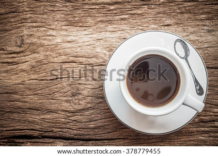 Close up overhead view of a cup of espresso coffee on a old wooden background. Vintage style. - stock photo