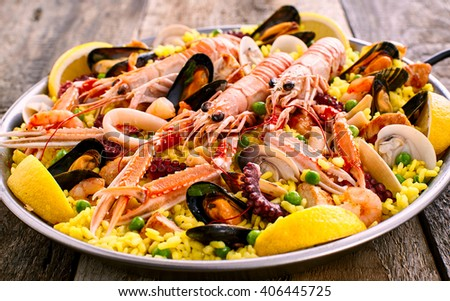 Close Up Overview of Colorful Spanish Seafood Paella Dish Served in Shallow Bowl on Rustic Wooden Table - stock photo