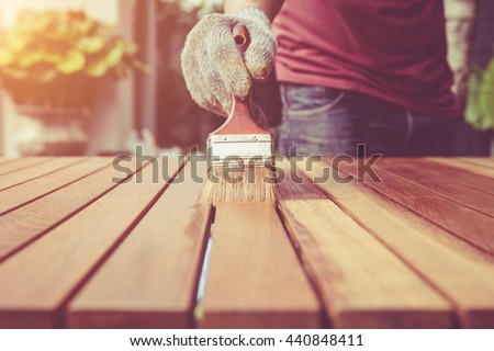 Close up paintbrush in hand and painting on the wooden table. Retro and vintage style - stock photo