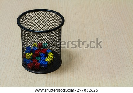 Close up paper tack in black basket on the wood background. - stock photo