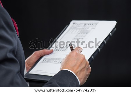 Close-up partial view of businessman holding papers and writing with pen