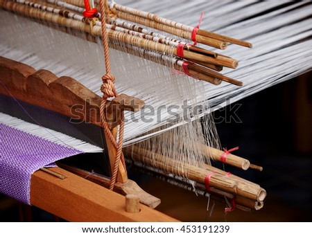 close-up parts of a manual small weaving machine and accessories for making traditional arts and crafts folklore textiles with natural hand made silk and cotton yarns in cultural village in THAILAND