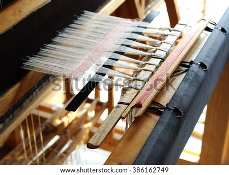 close-up parts of a manual small weaving machine for making education arts and crafts textiles with local traditional materials and yarns in a university's fashion and textiles workshop in THAILAND