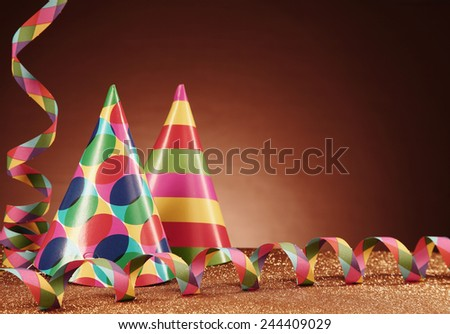 Close up Party Carnival Hats with Different Designs and Paper Streamers on Top of the Table, with Particles, in front Gradient Brown Background.